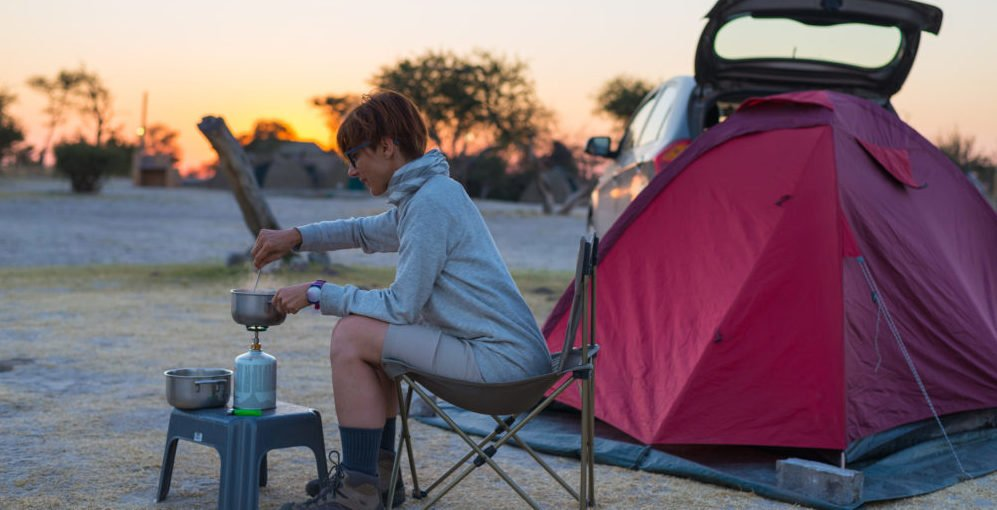 Woman cooking with gas stove in camping site at dusk. Gas burner, pot and smoke from boiling water, tent in the background. Adventures in african national parks.